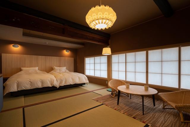 画像: 「近江屋」201号室のベッドルーム。障子越しの光が穏やかに室内を満たす。太い梁や欄間は、この建物の歴史を物語るもの。防音にも優れ、プライバシーはしっかり守られる