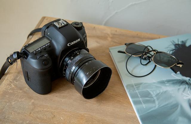 画像: 仕事の撮影のときはレンズを何本か持つが、プライベートで撮るときはキヤノンのカメラとレンズ1本だけ。「このカメラはまさに相棒。同じ機種を20年以上愛用しているので、何も考えずとも自分の筋肉のように使えるんです」。右は昨年刊行した写真集『ダレオド』