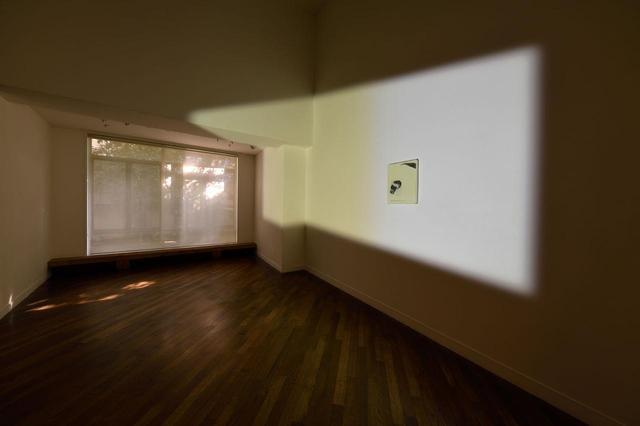 """画像: 活動拠点である台湾から持ってきた絵画を壁面に設置し、プロジェクターから光を投影したインスタレーション作品。「最初、光を正面から当ててみたら、いかにも""""アートっぽく""""なってしまって、つまらないなと。そこでプロジェクターを足でランダムに動かしてみたら、ユニークなライティングになったんです」とリー PHOTOGRAPH BY SHIGEO MUTO ⓒ LEE KIT, COURTESY THE ARTIST AND SHUGOARTS ほかの写真をみる"""