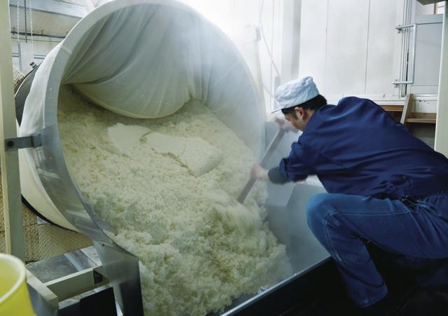 画像: 萱島酒造の「蒸し」の工程。100°C近い米を蒸し器から取り出し、広げて冷やす。1釜で750kg、1日3〜4tを蒸す。米を蒸す作業は重労働。蒸し時間や蒸し上がり具合が酒の香りや味わいを大きく左右する ほかの写真を見る