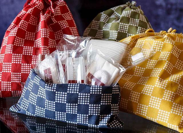 画像: 客室内に置かれたバスアメニティ。かわいい手提げ袋は4色揃い、持ち帰り自由。アメニティグッズを1つも使用しない場合は、ホテルはゲストに代わって地球保全活動基金団体に寄附するという PHOTOGRAPHS: © MITSUI GARDEN HOTELS ほかの写真をみる