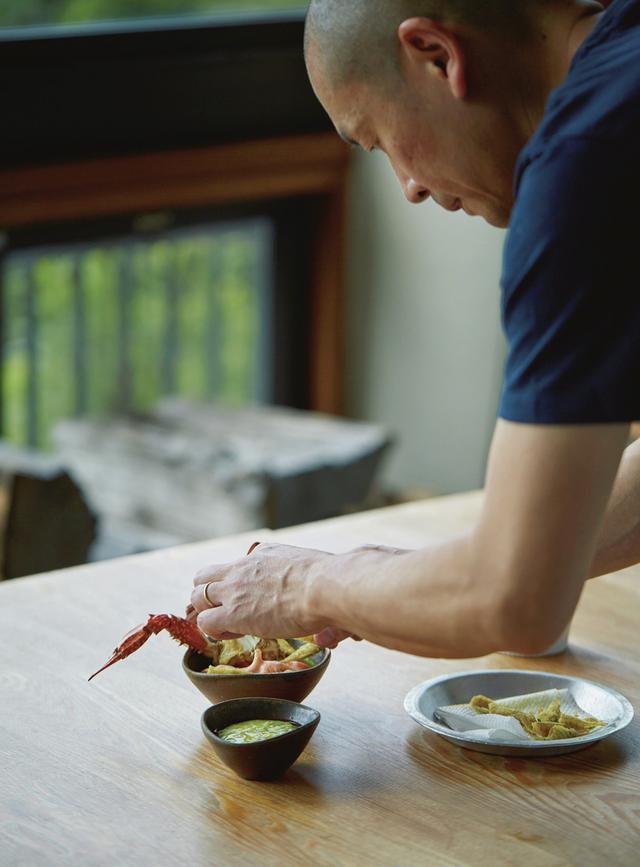 画像: 備前焼作家、伊勢㟢競作の中鉢にワタリガニを盛る林冬青シェフ。手前はズッキーニとヨーグルトのスープ ほかの写真を見る