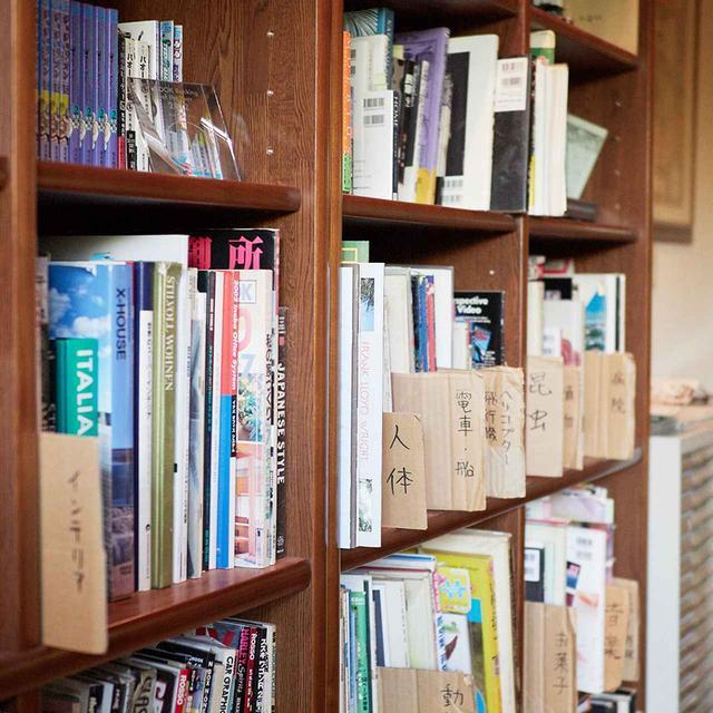 画像: アトリエの本棚には、世界各地の建築やインテリア、乗り物などの参考資料が並ぶ。なかには料理のマナー本もあり、徹底したリアリティを求める荒木のこだわりがうかがえる ほかの写真をみる