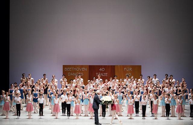 画像: ハンブルク・バレエ学校の総勢190名が出演した『ベートーヴェン・ダンス』終演後のカーテンコールで、生徒から花束を贈られるノイマイヤー PHOTOGRAPH BY KIRAN WEST