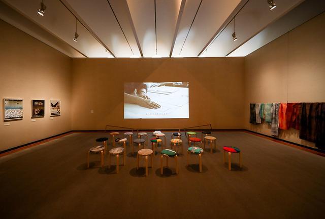 画像: 展示室ではヘルシンキの自宅で収録されたインタビュー映像も上映。アルヴァ・アアルトの名作スツールの座面には、石本デザインのテキスタイルが張られている。他に原画やドローイングをはじめ、色彩の実験や思考の軌跡をたどる展示も