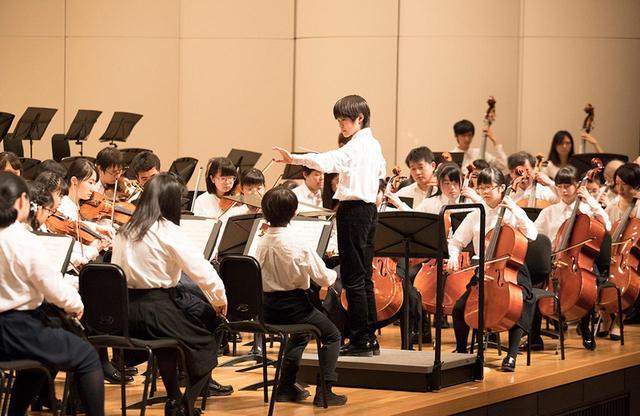 画像: 2018年3月、子ども音楽祭の舞台。相馬の子どもによる指揮で、グリーグ「ホルベルグ組曲」を演奏。中央で指揮をする少年は、取材チームが3年前に相馬を訪れたときは、ひときわあどけなさの目立つ男の子だった COURTESY OF EL SISTEMA JAPAN