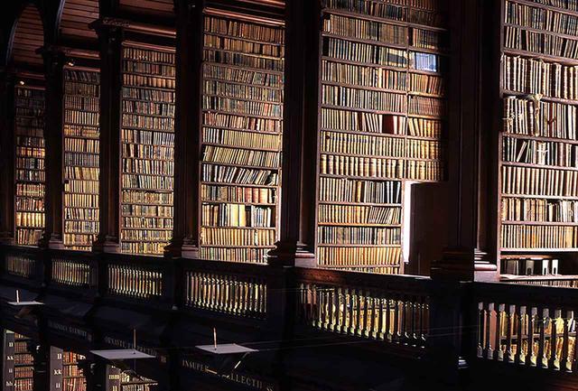 画像: ダブリン、トリニティカレッジの図書館。古色を帯びた書物が壁のように天井までそびえるさまは圧巻