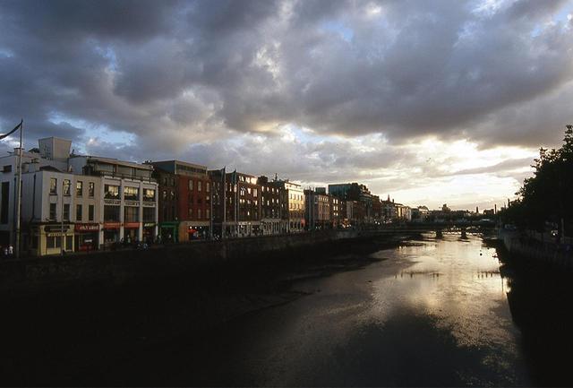 画像: ダブリンの街とリフィー川。垂れ込める雲が夕暮れの街を包む