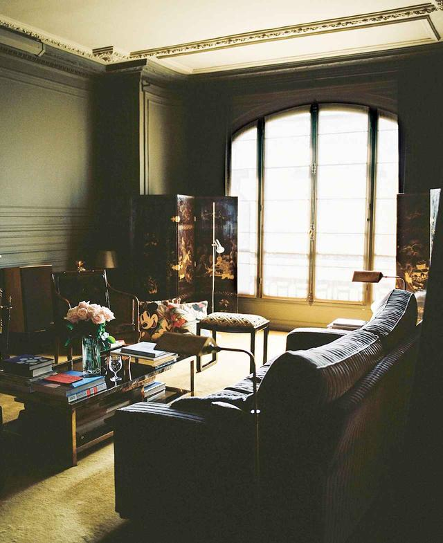 画像: リビングルーム。19世紀の中国の屛風、ゴダンが蚤の市で買った大きなテーブル、70年代のイヴ・サンローランの書斎にあったものを彷彿させるソファが置いてある。床一面に敷かれたカーペットは老舗「Codimat」に頼んだもの ほかの写真をみる