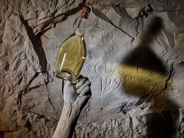 画像: セラーの壁面を背景にしたこの作品では、他とは異なり、自身の腕に壁と同じ白亜質の石灰を塗りつけている。「以前、彫刻作品を作っていたころは、私はいつも石灰まみれ。この土は、昔の自分をも思い起こさせました」とリウ。特に個人的な思い入れが強い一枚だと話す © RUINART/LIU BOLIN ほかの写真をみる