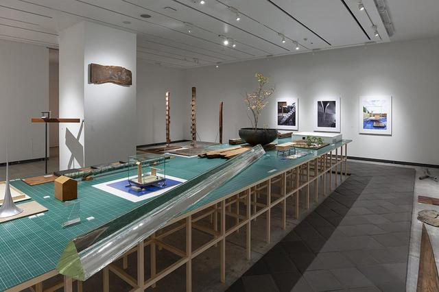 画像: 模型とともに新素材研究所が好む古材や道具、素材が置かれたテーブル。床面に敷かれている低焼成敷瓦は、東大寺の瓦を焼く奈良の鬼師に新素材研究所が特注したオリジナルの敷瓦