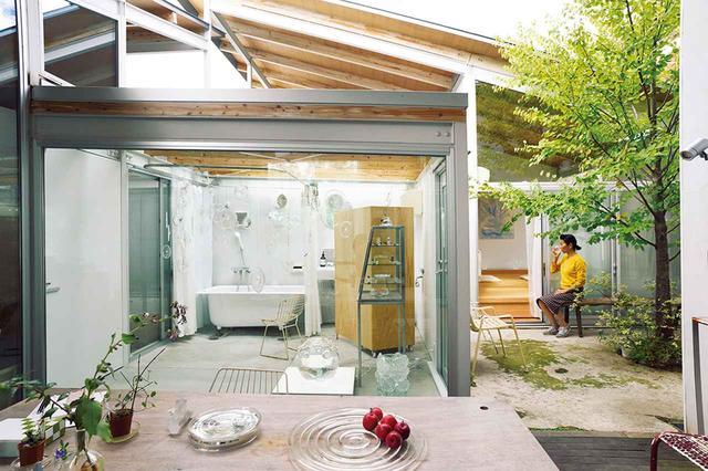 画像: リビングから見た三嶋りつ惠の家。テラスを囲んでキッチン、リビング、バスルームがつながる。京都での住居が西日本豪雨の被害に遭った三嶋は、ゲストハウスとして借りたこの家に仮住まい中 ほかの写真をみる