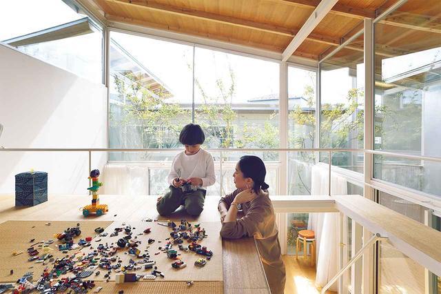 画像: ロフトは一人息子のエリスの遊び場。天井にあしらわれた木が、ガラスとコンクリートと鉄骨で作られた空間の印象を和らげる。隣家の屋根も景色の一部に ほかの写真をみる