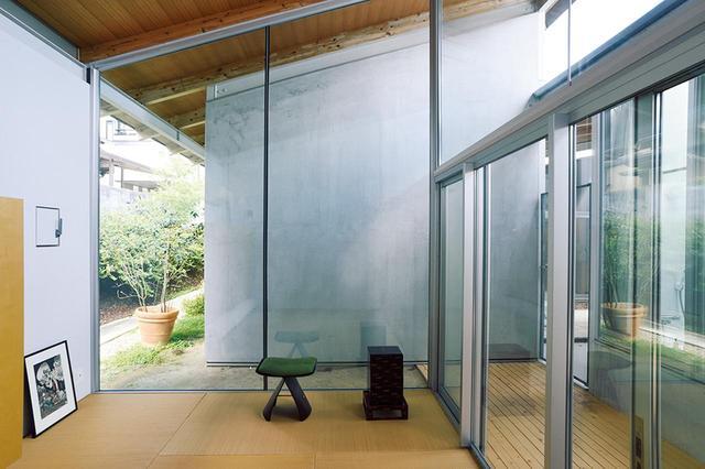 画像: 半屋外の通路を挟んだ和室には、柳宗理のバタフライチェアと京都の骨董市で見つけた装飾が美しい重箱が置かれている。左に床置きされたのは江戸時代の浮世絵 ほかの写真をみる