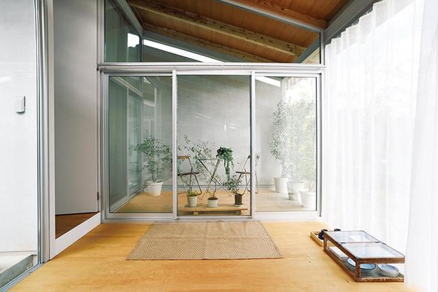 画像: キッチン&リビングの奥にもテラスがある。床置きしているガラス棚と食器は、京都の骨董市で購入した ほかの写真をみる
