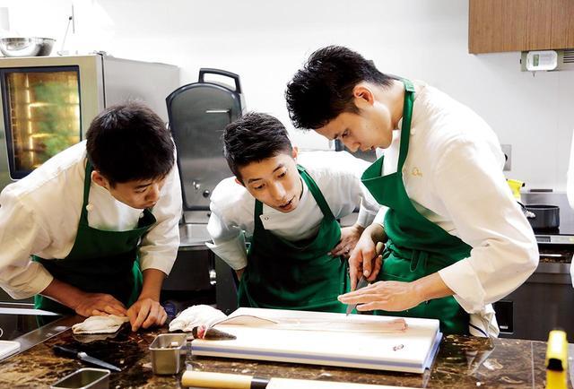 画像: 広い厨房のあちこちで、大樹や各店の料理長たちが料理を指導するシーンも。広尾本店のスタッフたちは、フランス料理の厨房ではなかなかお目にかかれないハモの骨切りを体験中。日本料理の技を取得するため、真剣な表情で代わるがわるトライ 他の写真もみる