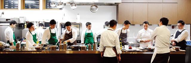 画像: 広い厨房で各自が料理に没頭する。緑のエプロンは広尾本店のスタッフ。茶色、白のエプロンは全国から集まった料理長たち