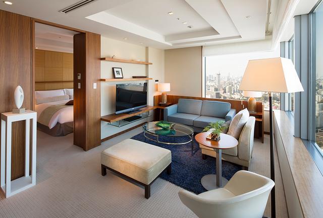 画像: 二面に窓がとられた明るい「The Suite」は70㎡の贅沢な客室。 リビングと寝室が別になっており、ゆったりと過ごせる。バスルームにはジャグジー完備。最大の部屋は、最上32階「ザ・ピークスイート」<104㎡>
