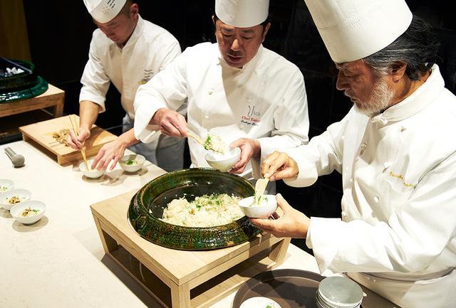 画像: コースの一品「焼きはまぐりごはん」を一緒にサーブする石鍋氏と紺野氏。大きな土鍋からハマグリの香ばしい風味が広がる