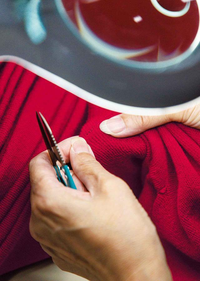 画像: 編み上がった3Dニットのワンピースに糸クズなどが混入していないか、人が検品する ほかの写真をみる