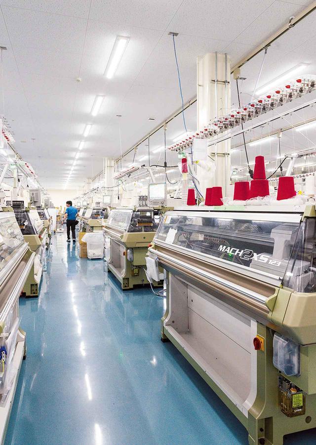 画像: 和歌山市内にある島精機製作所。 合弁会社契約の半年後にはすでに専門の工場を敷地内に建設していた。編み機が設置される部屋はゴミなどが付着しないよう整頓。近未来的な空間が広がる ほかの写真をみる