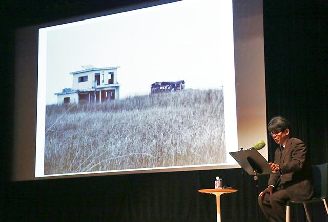 画像: 2018年11月末に行われた国際交流基金賞受賞講演会の細川俊夫氏。後方にはクリエイティブ・チームと福島を訪れた際の様子が映し出されている。この画像の建物がフィーブロックの舞台装置のモデルになったのだろう COURTESY OF THE JAPAN FOUNDATION 細川俊夫 1955年、広島生まれ。1976 年から10 年間ドイツに留学。ヨーロッパと日本を中心に作曲活動を展開し、世界の主要オーケストラ、音楽祭、歌劇場等からの委嘱が引きも切らない、日本を代表する作曲家。東日本大震災の犠牲者を悼む作品としては、ヴィオラのための『哀歌』(2011)、オーケストラのための『瞑想』(2012)、ソプラノとオーケストラのための『嘆き』(2013 )、オペラ『海、静かな海』(2014年、ドイツ・ハンブルク歌劇場初演)などがある