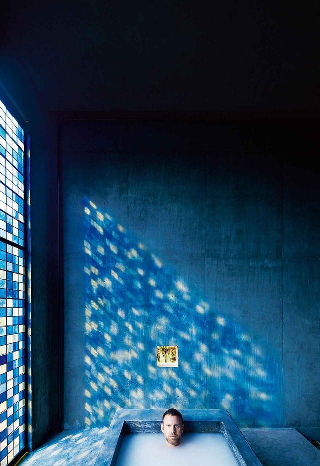 画像: クリスチャンセンが日課にしている入浴。浴槽は日の出の方向に面しており、その時間にステンドグラスの窓を通して、青色の影が西側の壁に映る。扉のように開く窓はロサンゼルスで手作りされたもの。浴室機器はウォーターワークス製