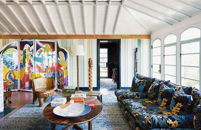 画像: リチャード・クリスチャンセンの1940年代風のロサンゼルスの家のリビングルームには、デイヴィッド・ホックニーの《カリビアン・ティー・タイム》の屛風式の作品がある。同じ部屋には、ベルギー人のデザイナー、JP・デメヤーのソファに、パリの蚤の市で手に入れたガブリエラ・クレスピのテーブル、イビサ島のホテルにあった象の形をした椅子、コンゴ共和国のアフリカの仮面、オズワルド・ボルサーニの暖炉用の器具も。壁の塗料はマディソン・アンド・グロウの特注