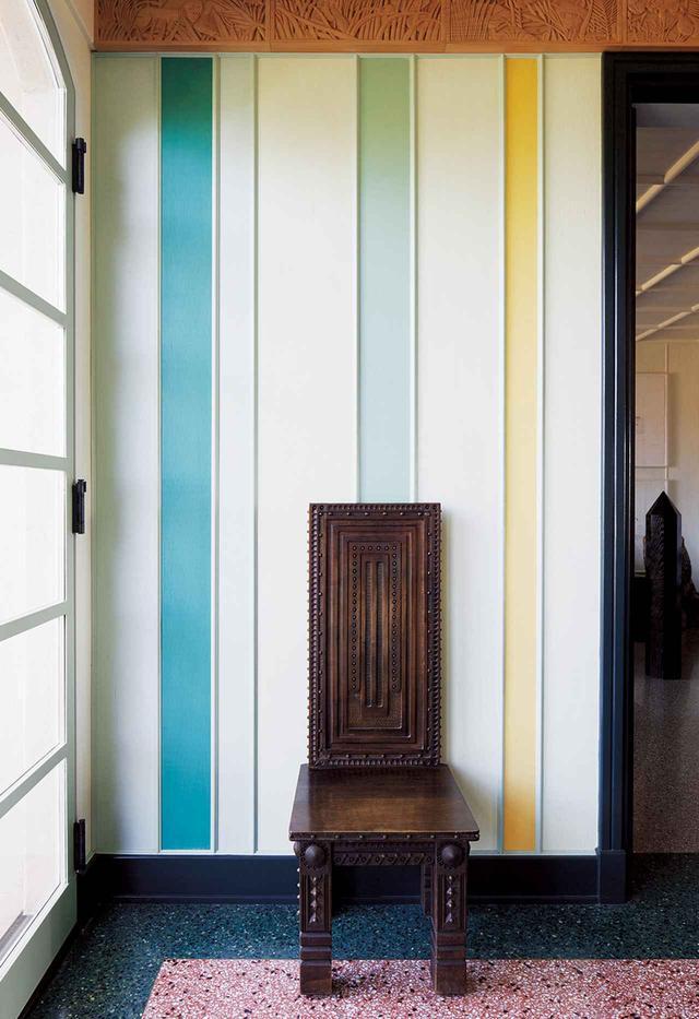 画像: パリの蚤の市で見つけたシンプルなアンティークの椅子が、複数の色のパネルで飾られた壁と、リビングルームの色鮮やかなテラゾが敷き詰められた床に映える