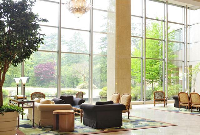 画像: 天井の高い吹き抜けのロビー空間は、全面ガラスの窓に迫る森との一体感が清々しい。シャンデリアや家具調度品にも高級感が漂う