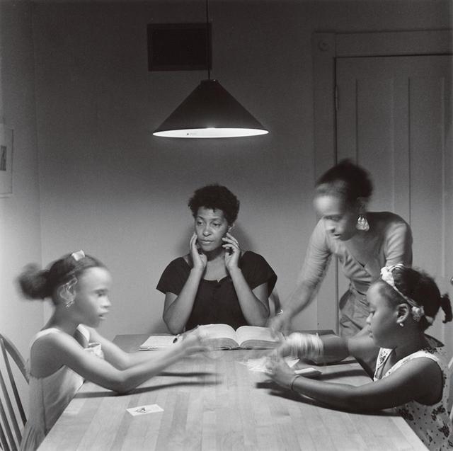 """画像: ウィームスの最も有名で、おそらく最も影響力のあるシリーズ『The Kitchen Table Series』からの作品。1989年から1990年の間に撮影されたこれらのイメージは、黒人のアイデンティティを親密さと細部にこだわって描いたもの。ウィームスが演じた、それぞれの写真の中心にいる女性がアイデンティティの核になっている 『Untitled(Woman and Daughter With Children)』 CARRIE MAE WEEMS, """"UNTITLED (WOMAN AND DAUGHTER WITH CHILDREN),"""" 1990 © CARRIE MAE WEEMS, COURTESY OF THE ARTIST AND JACK SHAINMAN GALLERY, NEW YORK"""