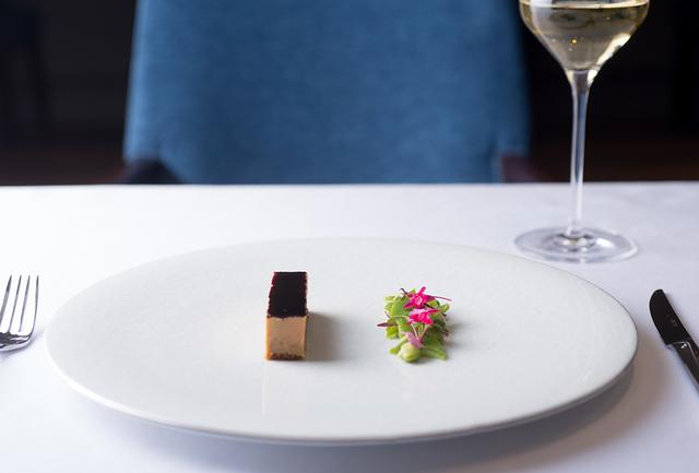 画像: 「フォアグラの冷製仕立て」 フォアグラのテリーヌに青い野菜を添えて。濃厚なテリーヌを、軽い塩味だけの爽やかな野菜が引き立てる。ナイフとフォークを入れやすいよう、フォアグラは左、野菜を右に盛り付ける。左利きの客には反対に盛る。最後まで緻密に計算されたひと皿。夜のコース¥18,000から