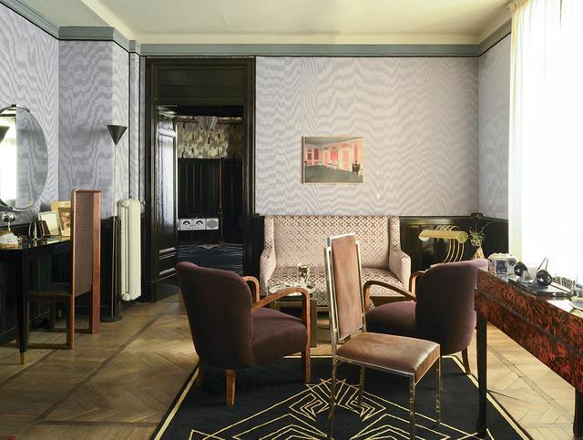 画像: ティルダ・スウィントン演じるマダム・ブランのアール・デコ調のリビングルーム。特徴的なモアレ柄の壁紙は、ミラノを拠点とするテキスタイルブランド「デダール」社によるもの