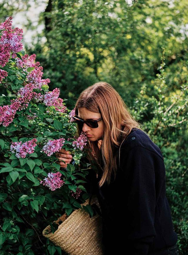 画像: 自宅とショップを結ぶ公園の裏手でライラックを見つけ、かけがえのない香りを吸い込むハリス。この花の芳香は「White」のインスピレーション源となった。「White」はパフューマー Hが2018年に発表した冬のフレグランスで、スエードや小麦粉の香調も用いられている