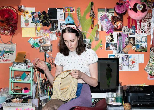画像: アトリエにいるハンリー。「服づくりはだいたい自分の手でやっているわね」と、自らの作品にラベルやボタン、刺繍を縫いつけながら話す ほかの写真もみる