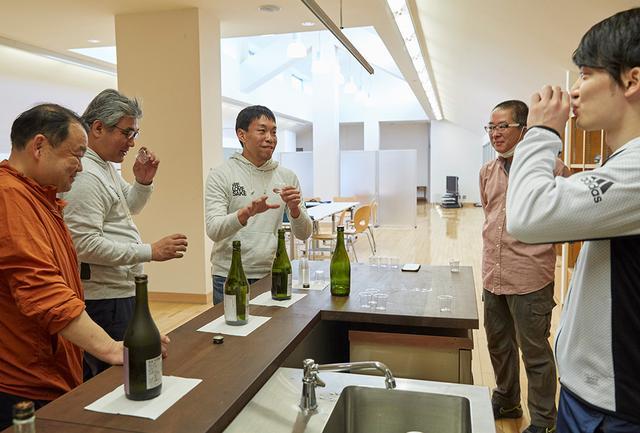 画像: 搾りの作業後は、北西酒造の酒の試飲タイム。応援団、髙島屋のほか北西酒造のスタッフもまじえて、「どんどん味の精度が上がってきているね」「生酛造りにも挑戦していますから、さらにがんばらないと」など、酒談義が弾む。左から3番目が日本酒応援団の代表・古原忠直氏
