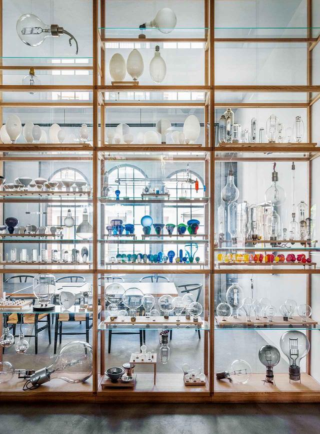 画像: キッチンとダイニングスペースを仕切る陳列用のガラス棚には、ヴィンテージの電球などのガラス製品がたくさん並べられている
