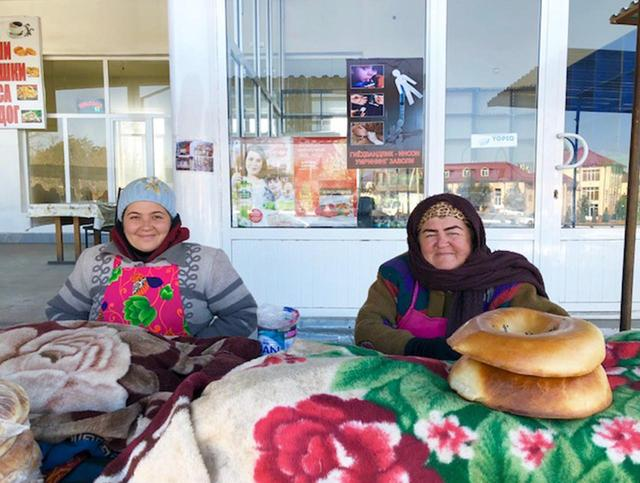 画像: パンを売る女性。ほかにもパン売りの屋台は数多く並んでいたが、色鮮やかな布を何枚もまとった彼女たちの笑顔に、思わず吸い寄せられてしまった