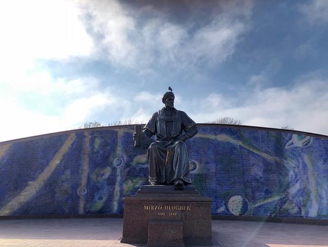 画像: ウグル・ベク像。その後ろのブルーのタイルには天体を描いたレリーフが施されている