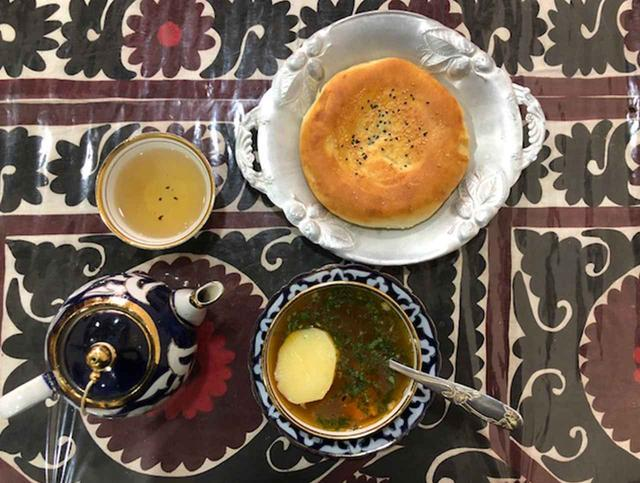 画像: 「ショールヴァ」という、肉や野菜がたくさん入った具だくさんスープ。パン、スープ、お茶をいただいて、約300円くらい。サマルカンド特有のスザニ(刺繍を施した布)をテーブルクロスやデコレーションに使用していて、食器も素朴で愛らしい