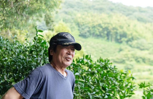 画像: 大谷農園の大谷元治さん。山の傾斜地で育てている柑橘の木を背景に。おおらかな雰囲気でゆったりと話すが、その言葉は深く哲学的だ