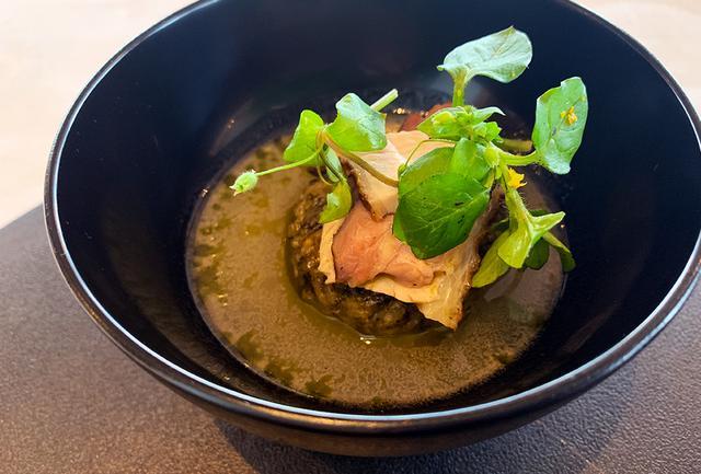 画像: 平田シェフによる肉の前菜「親密な風景」。フランス料理のコースに漆の椀が新鮮だ。ペアリングされたのは大きな片口から平盃に注がれた能登の地酒、数馬酒造の「竹葉」。「盃や椀で、いちばん敏感な唇に触れる漆の感触と日本酒、料理のマリアージュを楽しんでいただければ」と赤木さん PHOTOGRAPH BY JUNKO ASAKA