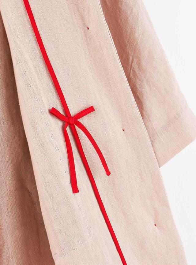 画像: 上のコートの内側にしのばされたリボン。脱いだとき、何かの拍子に服がめくれたとき、お祝いの贈りもののように真っ赤なリボンを見つけると楽しくなる。表からは見えない、うれしい秘密