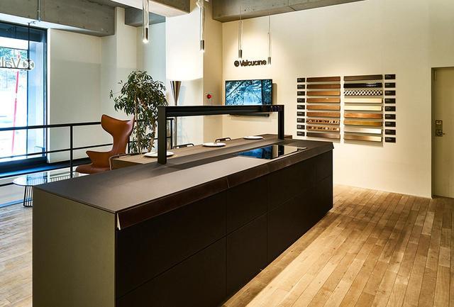 画像: シックな色のガラスで構成されたキッチンを展示する、外苑前の「ヴァルクッチーネ」ショールーム。壁には、キッチンにはめ込むことができる鍛金やモザイク、木象嵌、木彫などさまざまなイタリアの工芸パーツが飾られている