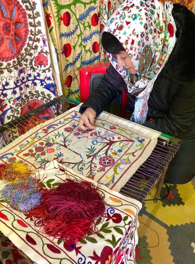 画像: 宮殿の外でスザニを売る女性。シルクで織られる色とりどりのモチーフの多くは、草花や果実を模したもの