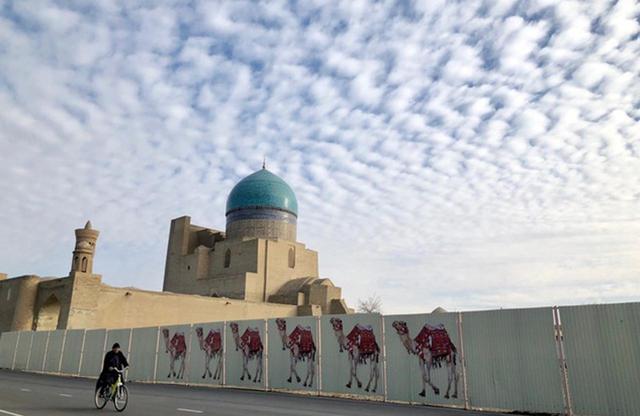 画像: アルク城へと向かう道。工事中なのだろうか、トタンの塀にラクダの群れが描かれているのがユーモラス