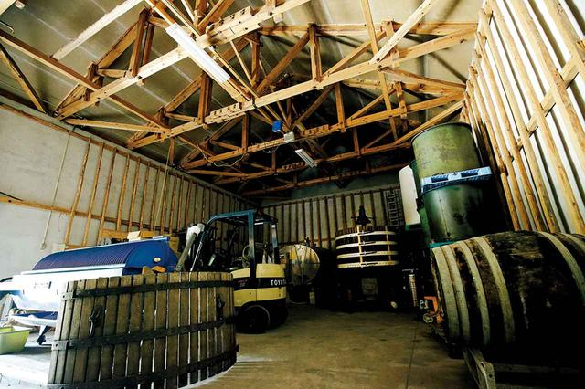 画像: 米倉庫を改造した醸造所。約100年前の木枠のプレス機と熟成用の樽は、中古品だが苦労してフランスから運んだもの。牛乳タンクを再利用した白ワイン醸造用タンク2台は、ネットオークションで各10万円。各5万円ほどで入手した日本酒タンク3台には赤ワイン用のぶどうを皮ごと漬け込んでいる