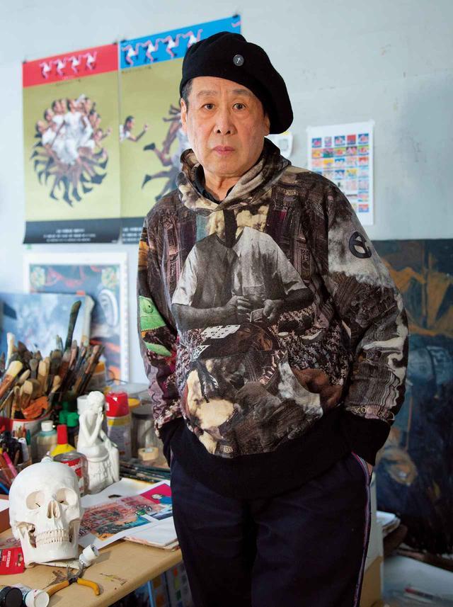 画像: 横尾忠則。アトリエにて。背後の壁にはデザインを手がけたNHK大河ドラマ『いだてん』のポスターが貼られている