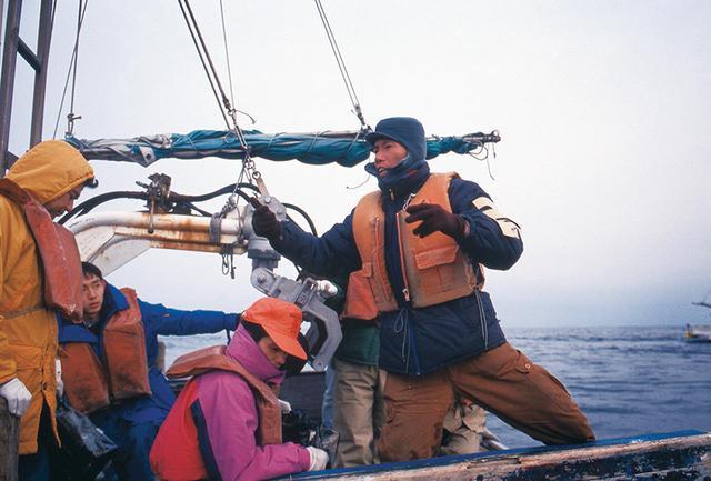 画像: 海に炎を走らせる《地平線プロジェクト》(1994年)のために船に乗り込んだ蔡。その後、見事に炎を走らせることに成功した PHOTOGRAPH BY KAZUO ONO