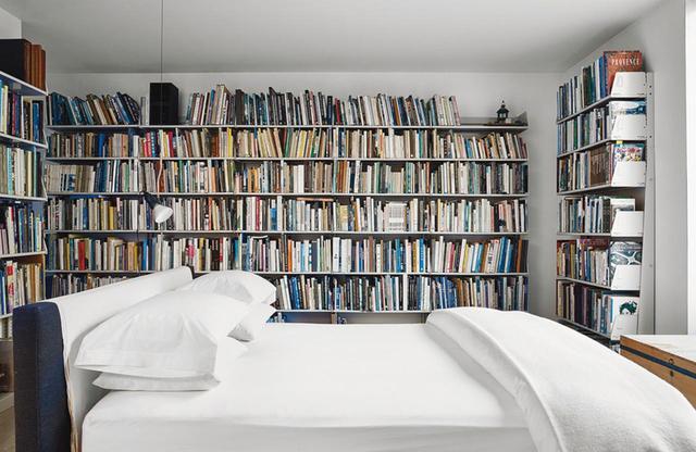 画像: ふたりが使うベッドのリネンは「デ・ポルトー」のもの。自在に組み替えられる棚は、モダン・オフィス・システム社製